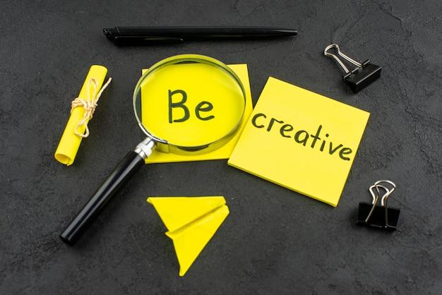 Vue de dessous soyez créatif écrit sur une note collante jaune, un stylo à pinces pour reliure lupa sur fond sombre