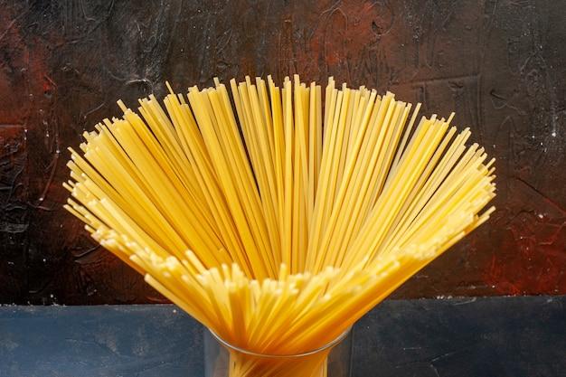 Vue de dessous des spaghettis en verre sur une table sombre
