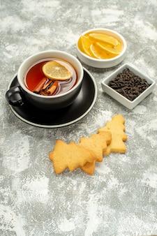 Vue de dessous une tasse de thé avec des bâtons de citron et de cannelle, un bol de biscuits avec des tranches de chocolat et de citron sur une surface grise
