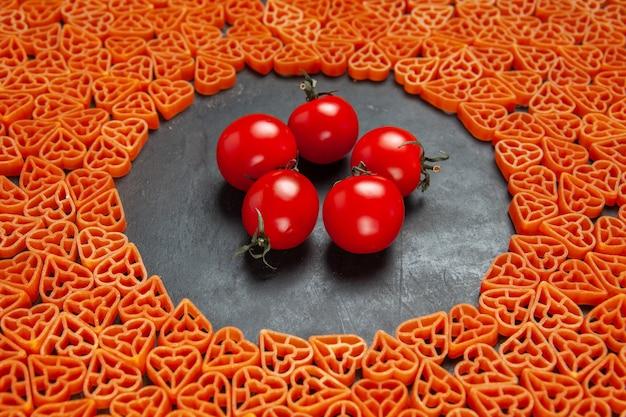 Vue de dessous des tomates de pâtes italiennes en forme de coeur sur un endroit vide ovale