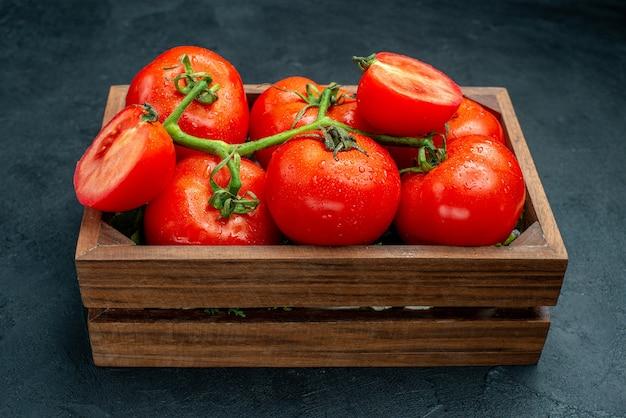 Vue de dessous des tomates rouges coupées des tomates dans une boîte en bois sur un tableau noir