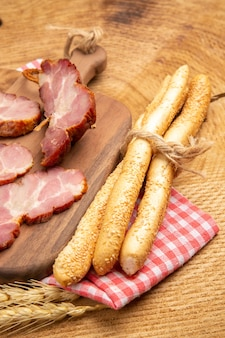 Vue de dessous des tranches de becon sur du pain de planche de bois sur une table en bois