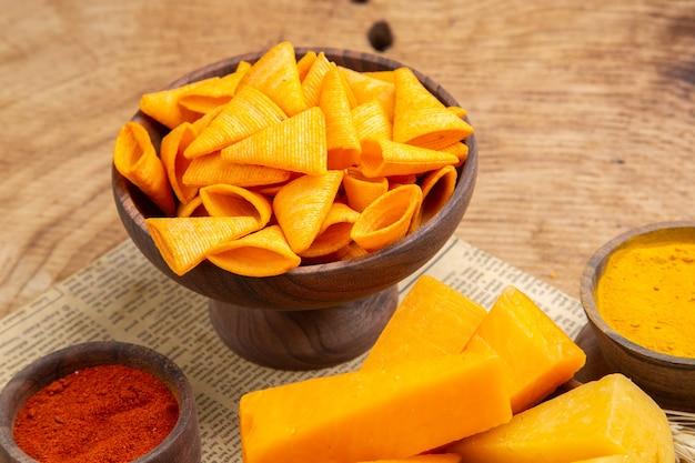 Vue de dessous tranches de fromage dans un bol poudre de poivron rouge chips épi de blé sur journal sur table isolée