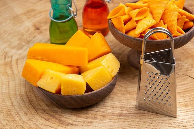 Vue de dessous des tranches de fromage et de frites dans des bols râpe de petites bouteilles sur un sol en bois