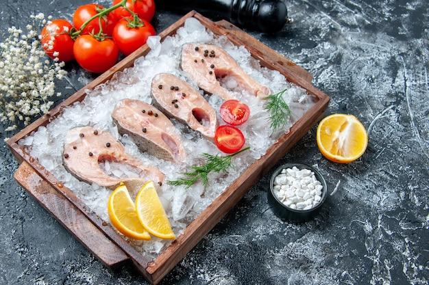 Vue de dessous des tranches de poisson cru avec de la glace sur planche de bois tomates moulin à poivre sel de mer sur table