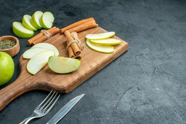 Vue de dessous des tranches de pomme et des bâtons de cannelle sur un couteau de planche à découper et une fourchette en poudre de menthe séchée dans un petit bol sur une table sombre avec un espace libre