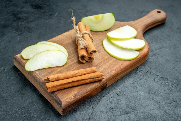 Vue de dessous des tranches de pomme et des bâtons de cannelle sur une planche à découper sur une table sombre