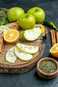 Vue de dessous tranches de pomme bâtons de cannelle et tranches de citron pomme sur planche de bois coupées citron cannelle menthe séchée dans un bol sur tableau noir