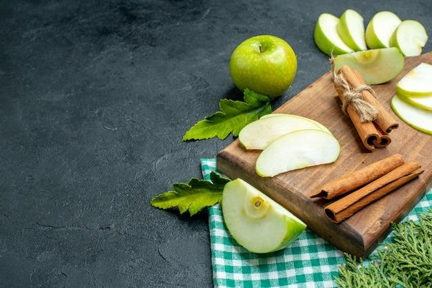 Vue de dessous des tranches de pomme et de la cannelle sur une planche à découper de la poudre de menthe séchée dans un petit bol de branches de pin de pomme sur un espace libre de table sombre