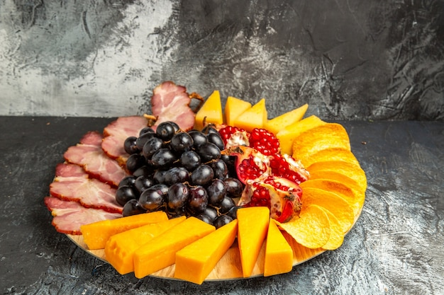 Vue de dessous tranches de viande, raisins au fromage et grenade sur un plateau de service ovale dans l'obscurité