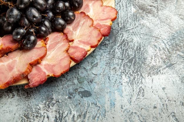 Vue de dessous des tranches de viande de raisins sur un plateau de service ovale sur un espace de copie de fond sombre