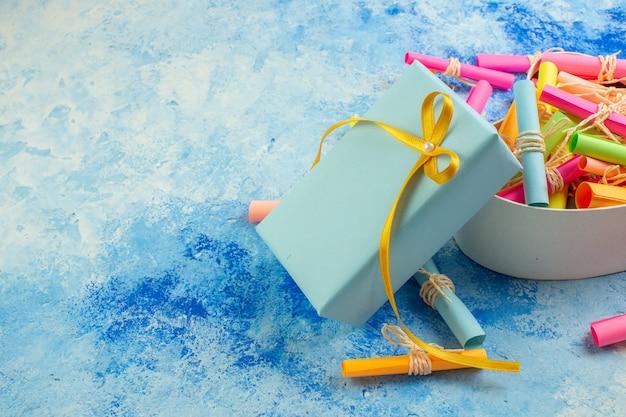 Vue de dessous valentines day concept faites défiler les papiers de souhaits dans une boîte en forme de coeur cadeau enveloppé sur fond bleu copie place