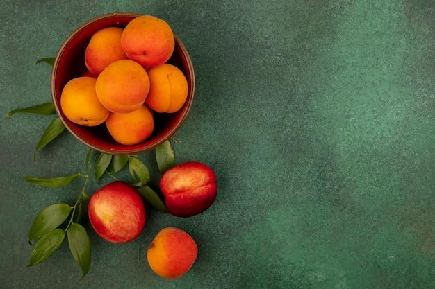 Vue de dessus des abricots dans un bol avec des pêches et des feuilles sur fond vert avec espace copie
