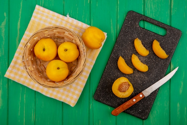 Vue de dessus des abricots entiers dans le panier et sur un tissu à carreaux avec la moitié et en tranches avec un couteau sur une planche à découper sur fond vert