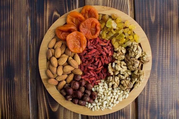 Vue de dessus des abricots secs, raisins secs, baies de goji, différentes noix sur la planche à découper ronde