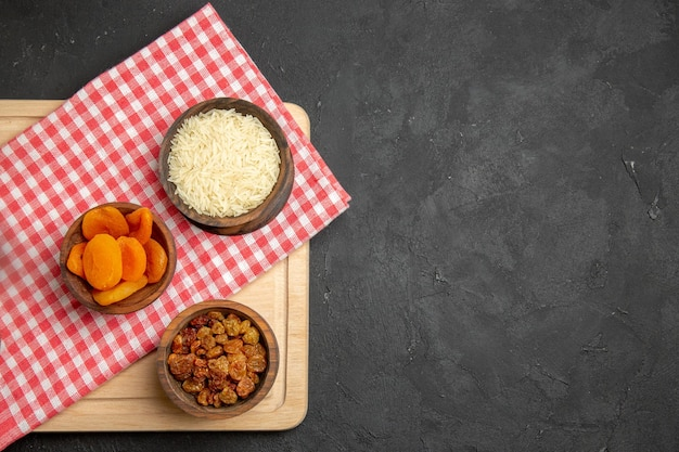 Vue de dessus des abricots secs avec des raisins secs et du riz sur une surface grise aux raisins secs