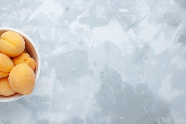 Vue de dessus des abricots sucrés frais fruits moelleux et délicieux à l'intérieur de la plaque sur un bureau léger, vitamine d'été de fruits frais