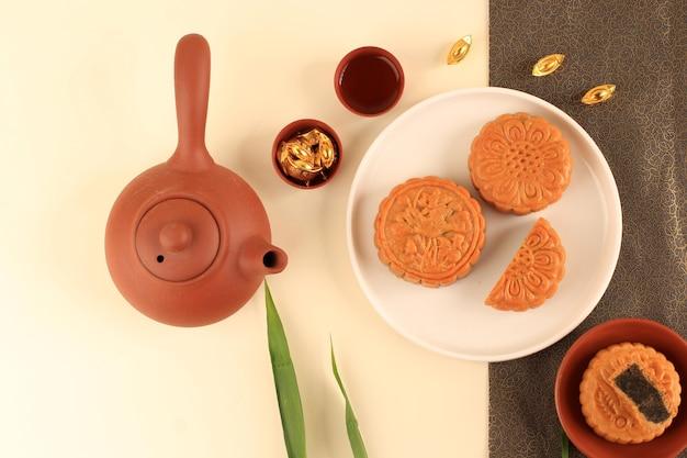 Vue de dessus abstract still life festival de la mi-automne snack moon cake sur fond crème avec jeune bambou, mise au point sélectionnée, espace de copie