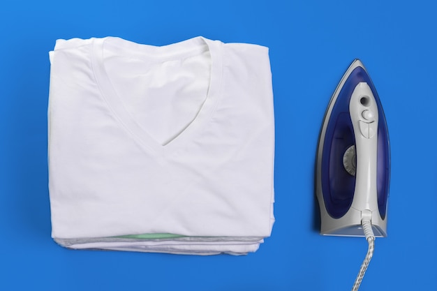 Vue de dessus abstraite du fer et des vêtements pour repasser sur fond bleu.