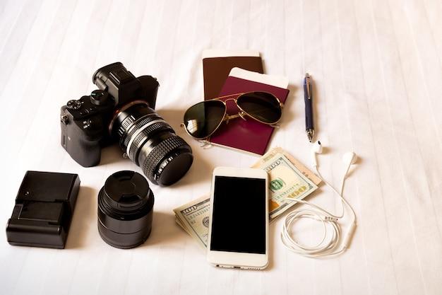 Vue de dessus de l'accessoire de voyageur sur le lit avec appareil photo numérique, smartphone, lunettes de soleil