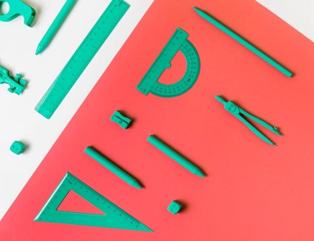 Vue de dessus des accessoires bleus minimaux de bureau sur fond rose