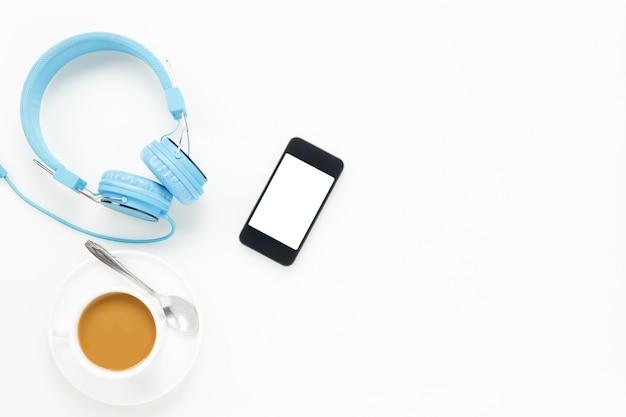Vue de dessus accessoires bureau bureau.smartphones casque et tasse de café sur fond blanc avec copie espace.
