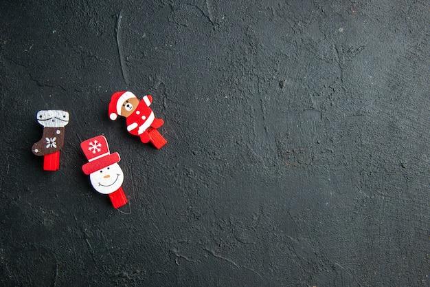 Vue de dessus des accessoires de décoration du nouvel an sur le côté gauche sur une surface noire
