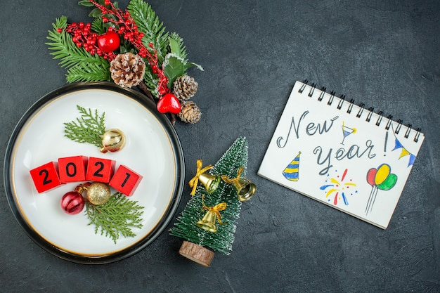 Vue de dessus des accessoires de décoration numéros sur une assiette branches de sapin conifère cône et cahier avec nouvel an écrit et dessin sur fond sombre