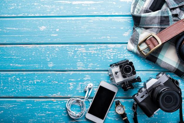 Vue de dessus des accessoires du voyageur, photographie laïque à plat du concept de voyage sur fond bleu