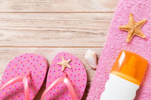 Vue de dessus des accessoires de plage à plat. bouteille de crème solaire avec coquillages, étoile de mer, serviette et tong sur fond de planche de bois avec espace de copie.
