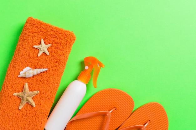 Vue de dessus des accessoires de pose à plat beach. bouteille de crème solaire avec des coquillages, des étoiles de mer, une serviette et une bascule sur fond coloré avec copie espace