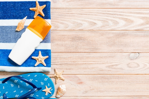 Vue de dessus des accessoires de pose à plat beach. bouteille de crème solaire avec des coquillages, des étoiles de mer, une serviette et une bascule sur fond de planche de bois avec copie espace