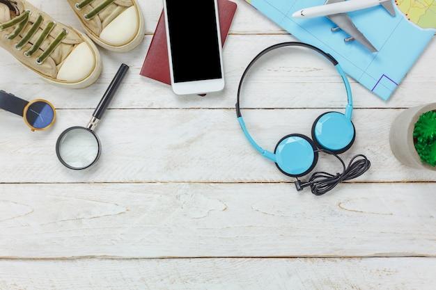 Vue de dessus des accessoires pour le concept de voyage. téléphone portable et casque sur fond en bois.