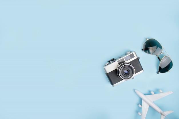 Vue de dessus des accessoires pour touristes avec appareils photo argentiques, lunettes de soleil et avion supérieur