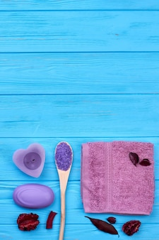 Vue de dessus des accessoires de salle de bain spa à plat et espace de copie. fond de bureau en bois bleu tir vertical.