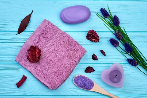 Vue de dessus des accessoires de spa aromatiques sur un bureau en bois bleu. savon violet à plat avec bougie et serviette.