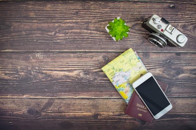 Vue de dessus des accessoires touristiques avec appareils photo argentiques, cartes, passeports et smartphones.