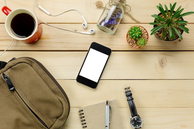 Vue de dessus accessoires voyage avec téléphone mobile, lunettes de soleil, sac, montre, notepaper, écouteurs, stylo, cactus, café sur table en bois avec copie space.travel concept.