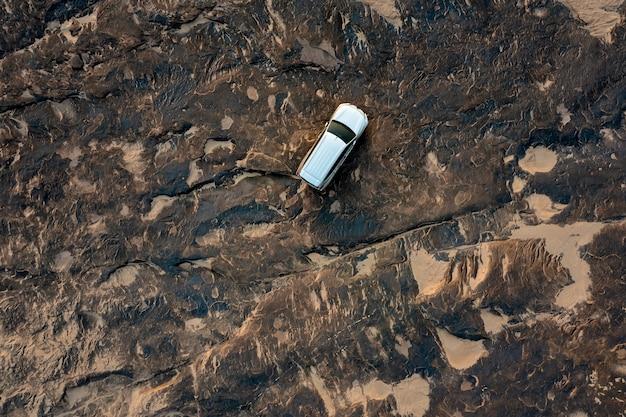 Vue de dessus aérienne petite voiture suv hors route et résumé de fond de pierre de roche du grand canyon