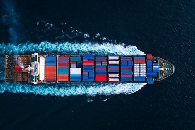 Vue de dessus aérienne porte-conteneurs à pleine vitesse dans la mer d'un bleu profond pour la logistique de fret transport d'importation et d'exportation international asie pacifique