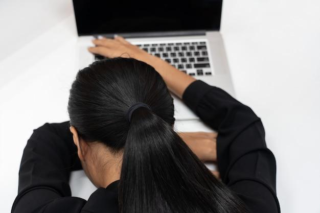 Vue de dessus des affaires fatiguées femme asiatique dormir devant son ordinateur portable