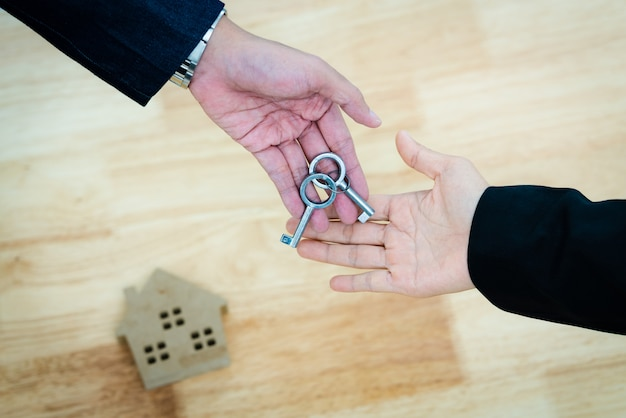 Vue de dessus agent immobilier donne la clé de la maison à un couple après signature du contrat de prêt
