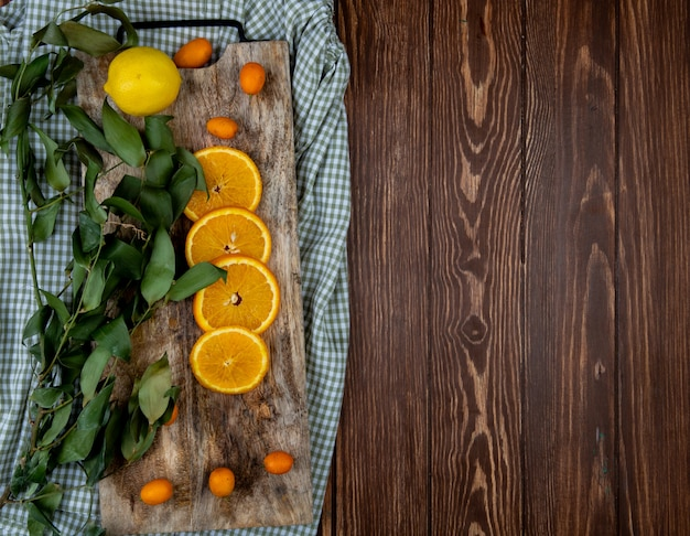 Vue de dessus des agrumes comme kumquat citron orange avec des feuilles sur une planche à découper sur un tissu et un fond en bois avec copie espace