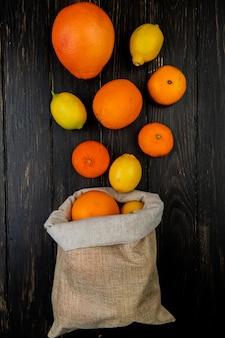 Vue de dessus des agrumes comme pamplemousse citron mandarine débordant de sac sur fond de bois