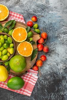 Vue de dessus agrumes pommes agrumes sur la planche sur la nappe à carreaux cerises
