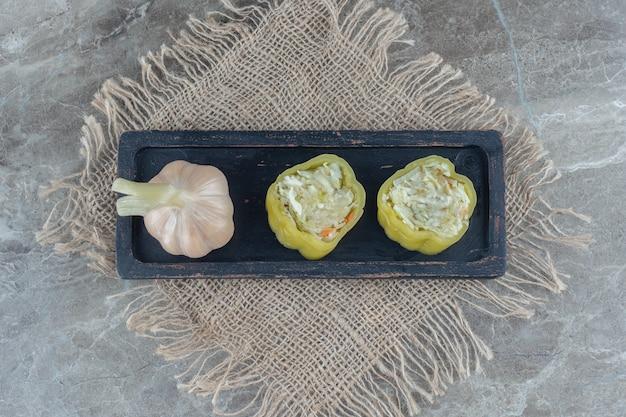 Vue de dessus de l'ail en conserve et du poivre rempli sur une plaque en bois.