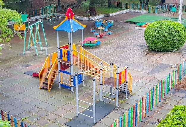 Vue de dessus d'une aire de jeux pour enfants colorée et vide dans un parc public, balançoires sûres, toboggans.