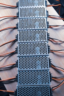 La vue de dessus de l'alimentation en treillis métallique du microcircuit se trouve sur une table en bois lors de la production d'ordinateurs de haute technologie. concept de haute technologie et équipement de bureau