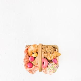 Une vue de dessus des aliments cuits et sucrés dans le panier sur le fond blanc