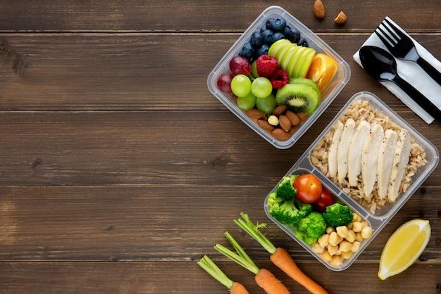 Vue de dessus d'aliments sains riches en éléments nutritifs dans des boîtes à emporter sur fond de table en bois avec copie espace